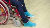 severely : Caucasian female trying to put her legs wearing blue shoes on the wheelchair step, closeup view