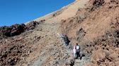 ada : TEIDE, TENERIFE - CIRCA JAN, 2016: Beginning of route No. 10 (Telesforo Bravo) to the crater of Teide, to Spains highest peak. People with young child walk to summit. Stok Video