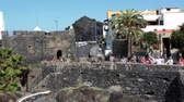 small : GARACHICO, TENERIFE, SPAIN-CIRCA JAN, 2016: Castillo de San Miguel fortress is on the embankment of Garachico town. Visitors walk on shore. The Garachico is an ancient town on the north of island