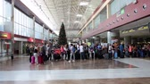 ada : REINA SOFIA AIRPORT, TENERIFE, SPAIN - CIRCA JAN, 2016: Passengers stand in queue to boarding gate in the Tenerife-South International airport TFS. Christmas eve