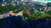 naturalistic : Lighthouse standing on a mountain above a small city in Australia Forest. Beach. Aerial top view