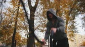 cabelo curto : Young athlete in Hoodie trains with battle ropes in the autumn park Vídeos