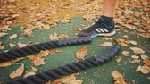 catcheur : A young athlete walks over and takes a ropes in yellow leaves in a park.