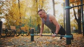 push ups : Young athlete does not push up exercise wide honor in autumn park Stock Footage
