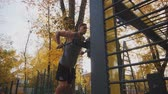 párhuzamos : Young athlete does exercise on parallel leopard in autumn park Stock mozgókép