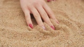 girl driving her fingers along the sand