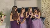 besties : Emotional bridesmaids look at the boutonniere on their hands, talking and laughing during the morning of the bride in a photo studio. Girls in purple wedding dresses sitting on the studio couch.
