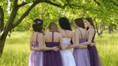 besties : Look from behind of emotional bride and bridesmaids that talking and smiling. Caucasian girls in purple dresses posing outdoors.