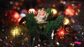 papai noel : Miniature Santa Claus figure between four toy Hanging Baubles for a Christmas tree. Golden Santa on artificial Christmas tree surrounded by flashing lights. Stock Footage