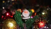 bombki : A small silver figure of Santa Claus stands near a red Christmas Hanging Bauble on artificial Christmas tree. Christmas garlands blink in the foreground and background.