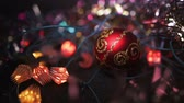 bokeh : Christmas and New Year Decoration. Hanging Bauble close up. Abstract Blurred Bokeh Holiday Background. A red toy ball for a Xmas tree lies on a wooden surface surrounded by garlands. Stock Footage