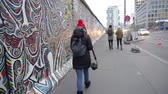 comunismo : BERLIN, GERMANY - NOV 22, 2018: Woman with a camera walks near Berlin Wall. Slow motion. Vídeos