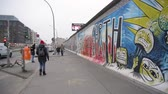 segmento : BERLIN, GERMANY - NOV 22, 2018: Trendy tourist walks near Berlin Wall. Slow motion.