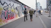 BERLIN, GERMANY - NOV 22, 2018: Young couple walks near Berlin Wall. Slow motion. Стоковые видеозаписи