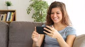 видя : Happy girl watching media content on a smart phone after choosing it sitting on a couch at home
