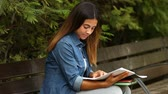 campus : Student studying in a park reading notes