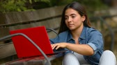 campus : Concentrated woman typing on a laptop on a bench in a park Stock Footage