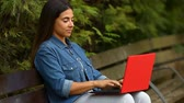 escritor : Happy woman chating online with a laptop and laughing sitting on a bench in a park