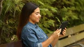 aquisitivo : Happy woman using a tablet to browse media content and laughs sitting on a bench in a park Stock Footage