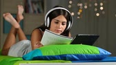 campus : Teen e-learning comparing to tablet and notebook notes lying on a bed in the night at home