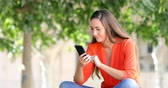 leilão : Excited woman using a smart phone finding good news sitting on a bench in a park