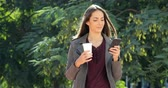 genético : Woman using a smart phone and holding a drink in a park
