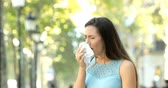 infecção : Ill woman sneezing covering mouth with a tissue in the street Vídeos