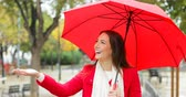 meteorologia : Front view portrait of a happy woman in red walking holding an umbrella under the rain in winter Stock Footage
