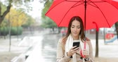 guarda chuva : Front view portrait of a serious woman checking smart phone walking holding a red umbrella under the rain