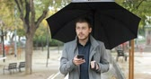 guarda chuva : Front view portrait of a frustrated man checking weather on a smart phone in the rainy day in a park