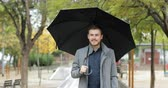 bem estar : Front view portrait of a happy man walking holding an umbrella under the rain in winter in a park