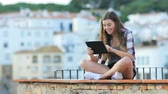 entreter : Happy teenage girl using a tablet sitting on a ledge in a coast town on vacation