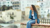 destino : Happy woman contemplating ocean from a ledge in a coast town