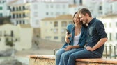 bud : Happy couple listening to music from a smart phone sharing earphones sitting on a ledge in a coast town at sunset