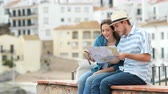 ask : Happy couple of tourists checking map and contemplating views sitting on a ledge in a coast town Stock Footage