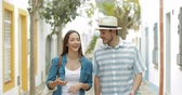 ask : Couple of tourists walking and talking on a town street on vacation Stock Footage