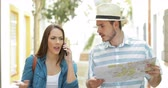 anger : Angry tourists claiming talking on phone walking towards camera in the street Stock Footage
