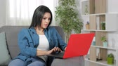notificação : Surprised woman finding content on laptop sitting on couch at home Vídeos