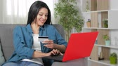 senha : Happy woman paying with credit card and laptop sitting on couch at home Stock Footage
