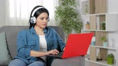 série : Serious woman with headphones browsing laptop sitting on couch at home