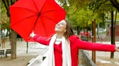 spirit : Happy woman in red enjoying under the rain holding an umbrella