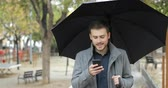 stres : Disappointed man receiving wrong phone message in the rainy day walking in the street