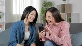 parente : Two happy women laughing reading smart phone content sitting on couch in the living room at home
