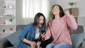 promoção : Excited women reading good news on a smart phone sitting on a couch in the living room at home