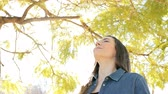 aide sociale : Happy relaxed woman breathing in fresh air standing in a park