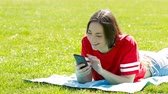 střední škola : Happy teenage girl in red checking phone lying on the grass in a park