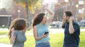 life is good : Excited friends jumping in the street after checking smart phone content