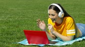 Teenage girl having a video call with a laptop on the grass