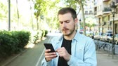 annoyed : Dissatisfied man uses smart phone in the street and after some time looks at camera with thumb down