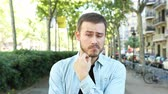 indifferent : Front view portrait of a doubtful man listening to you in the street Stock Footage